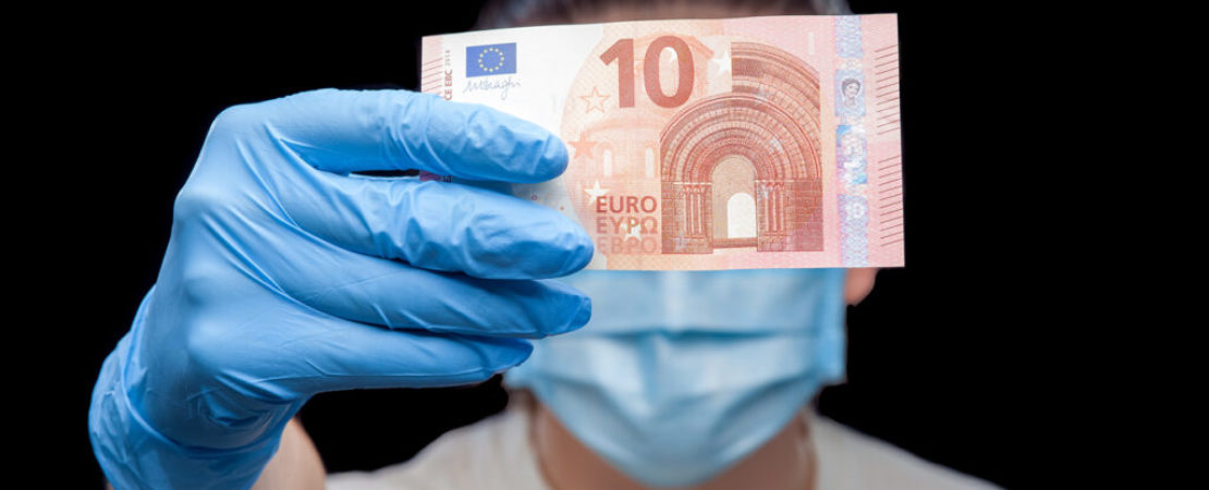 Portrait of a doctor in a medical mask and surgical glove hold a banknote ten Euro, close up of a conceptual background on the topic of corruption in medical medicine.